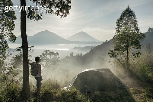 Asia, Indonesia, Bali, young woman standing in mist, next to tent, looking at the view while camping on Kintamani ridge, in front of Mount Agung volcano, at sunrise - gettyimageskorea