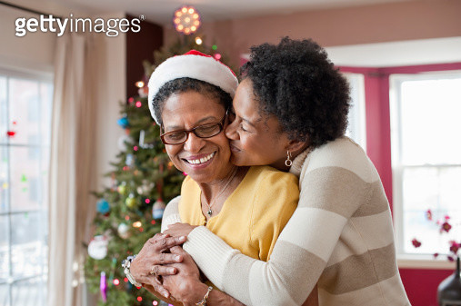 senior woman wearing Santa hat standing in front of Christmas tree with her adult daughter - gettyimageskorea