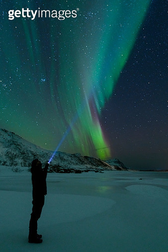 Man with a flashlight looking at Northern Lights, Aurora Borealis over the Lofoten - gettyimageskorea