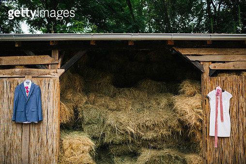 Wedding dress and grooms suit hanging on barn with hay - gettyimageskorea