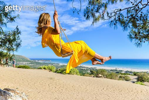 Woman in yellow dress on swing. - gettyimageskorea