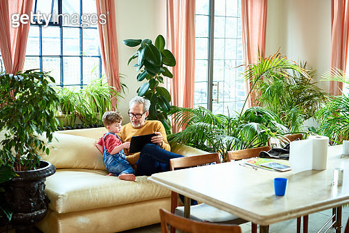 Grandson sitting with granddad and using device, playing mobile app online, technology, learning, education - gettyimageskorea
