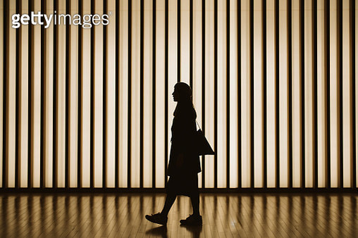 Silhouette of woman walking in front of striped illuminated wall - gettyimageskorea