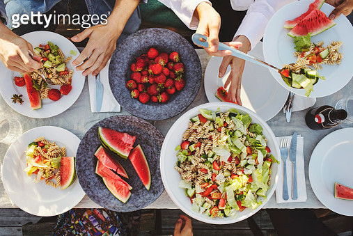 Directly above shot of friends enjoying lunch at picnic table on sunny day - gettyimageskorea