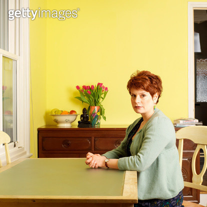 Woman sitting at kitchen table - gettyimageskorea