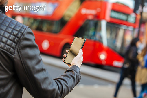 Using mobile phone on the street with red double decker bus in background, close up - gettyimageskorea