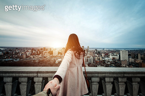 Happy traveller couple holding hands enjoying the spectacular city skyline of Montreal from view point - gettyimageskorea