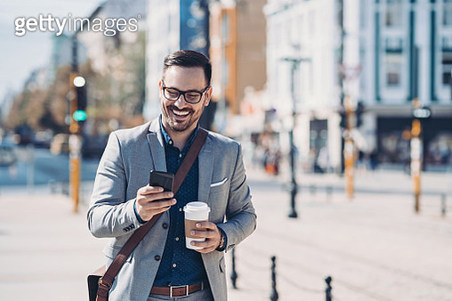Smiling businessman outdoors in the city - gettyimageskorea