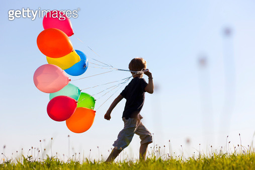 Boy with colorful balloons in grass - gettyimageskorea