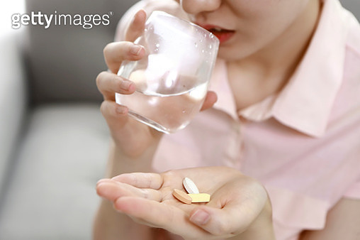 Close-up of woman taking pills - gettyimageskorea