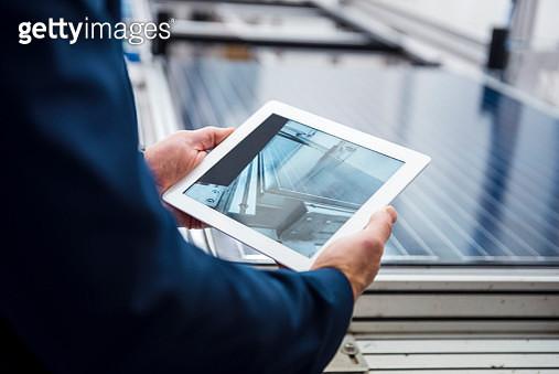 Businessman in solar factory holding tablet - gettyimageskorea