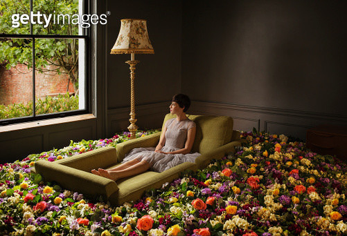 Woman sitting on sofa surrounded by flowers - gettyimageskorea
