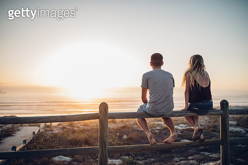 Rear View Of Couple Sitting On Railing Against Beach - gettyimageskorea