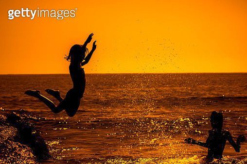 Happy young  girl jumping into the sea. - gettyimageskorea