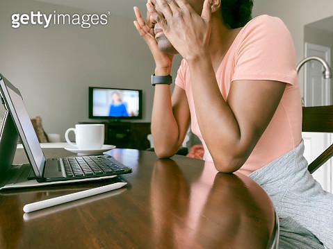 Close-up of mid adult black woman in self-isolation working on digital tablet at kitchen table with tv on in background - gettyimageskorea