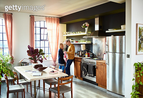 Mature couple chatting in kitchen and doing the dishes - gettyimageskorea