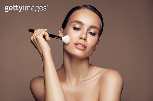 Beautiful young woman applying foundation powder - gettyimageskorea
