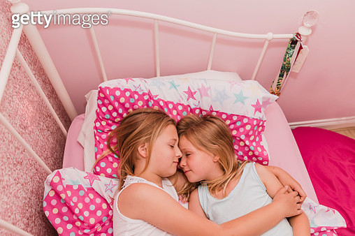 Two little sisters resting on bed - gettyimageskorea