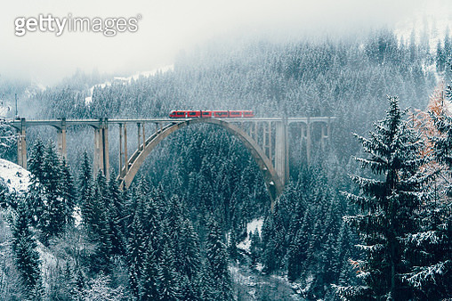 Scenic view of train on viaduct in Switzerland forest in winter - gettyimageskorea