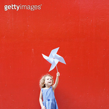 Smiling girl holding a pinwheel in the air making a Hong Kong flag - gettyimageskorea