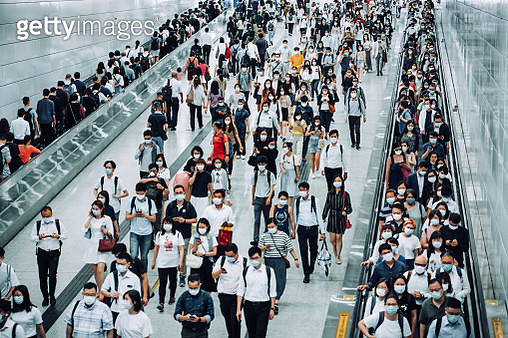 Crowd of busy commuters with protective face mask walking through platforms at subway station during office peak hours in the city - gettyimageskorea