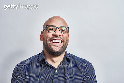 A studio portrait of a mixed race British male with stubble and glasses laughing with his head back. - gettyimageskorea