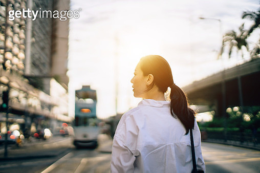 Beautiful young woman waiting for transportation ride on city street at sunset - gettyimageskorea