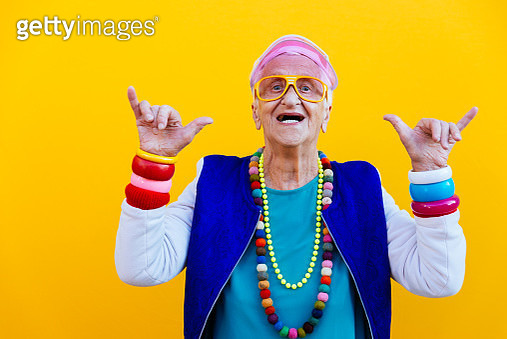 Portrait Of Senior Woman Wearing Colorful Jewelry Standing Against Yellow Background - gettyimageskorea