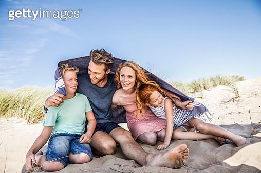 Netherlands, Zandvoort, happy family under a blanket on the beach - gettyimageskorea