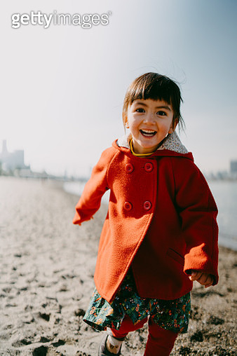 Portrait of happy little girl on beach in winter, Tokyo - gettyimageskorea