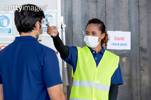 Warehouse worker woman use infrared thermometer measure temperature of worker man - gettyimageskorea