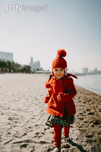 Happy little girl running towards camera on beach in winter, Tokyo - gettyimageskorea