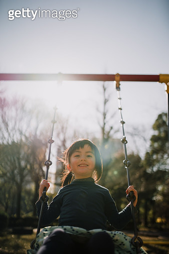 Cute mixed race little girl playing on swing, Tokyo - gettyimageskorea
