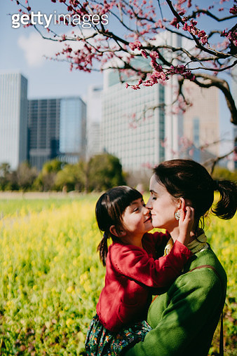 Mother and daughter having intimate moment under plum blossoms - gettyimageskorea
