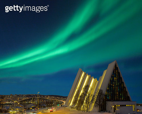 Illuminated Tromso cathedral at night with beautiful green shapes of aurora borealis - gettyimageskorea
