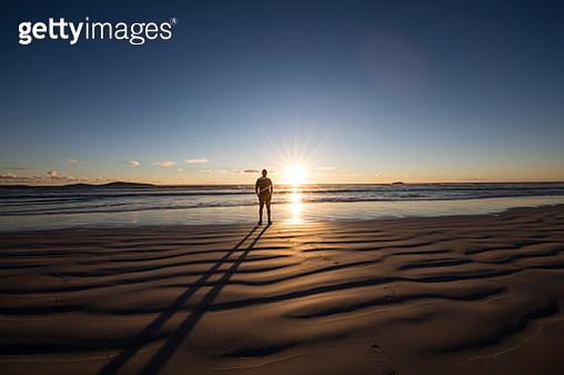 Man standing on beech looking at the sunset, Western Australia, Australia - gettyimageskorea