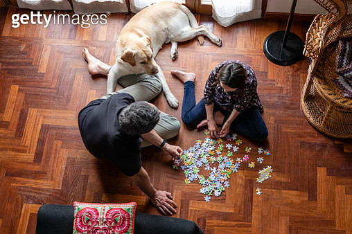 Father and daughter sitting on living room floor, doing jigsaw puzzle during Coronavirus lockdown. - gettyimageskorea