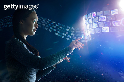 Young woman standing and pointing at floating applications, with glowing data swirling around her - gettyimageskorea
