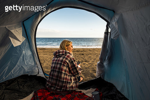 Woman Sitting In Tent At Beach Against Sky - gettyimageskorea