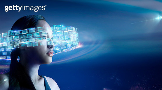 Young woman standing with glowing data that looks like many small tv screens swirling around her - gettyimageskorea