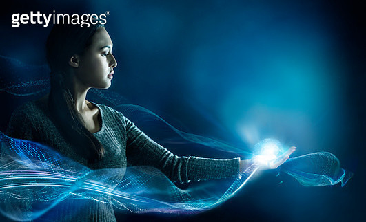 Young woman standing with her arm stretched, with glowing data swirling around her - gettyimageskorea