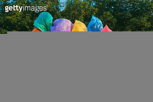 Young women in color plastic bags on their heads, in color sweaters and shorts - gettyimageskorea