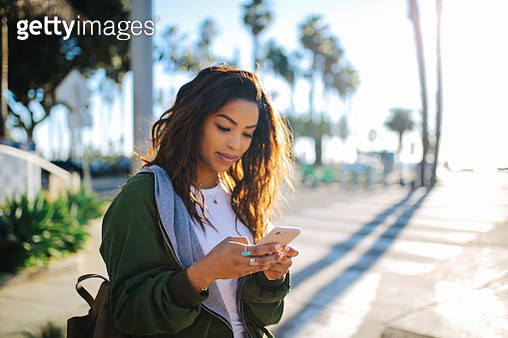 young fashionable woman reading a message on her phone in Santa Monica, LA - gettyimageskorea