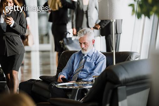 Senior Businessman Using Smart Phone At Airport - gettyimageskorea
