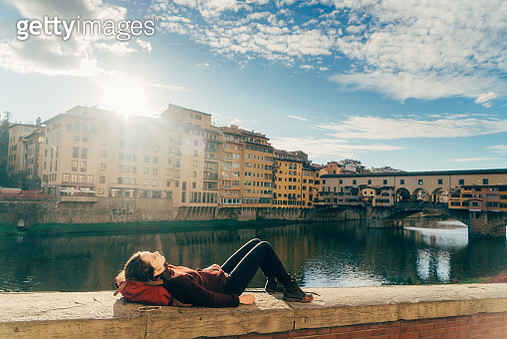 Young Caucasian woman resting with view on Ponte Vecchio  of Florence, Italy - gettyimageskorea