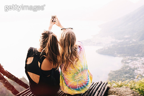 Rear view of two female friends taking smartphone selfie at Lake Atitlan, Guatemala - gettyimageskorea