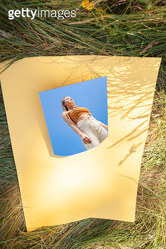 Mirror with reflection of woman on paper on grass - gettyimageskorea