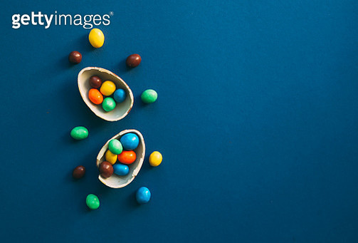 Chocolate Easter Eggs with colorful candies over classic dark blue background - gettyimageskorea