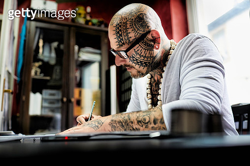 Tattooist working on draft at desk in his studio - gettyimageskorea