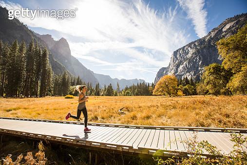 A woman jogging a boardwalk in Yosemite. - gettyimageskorea